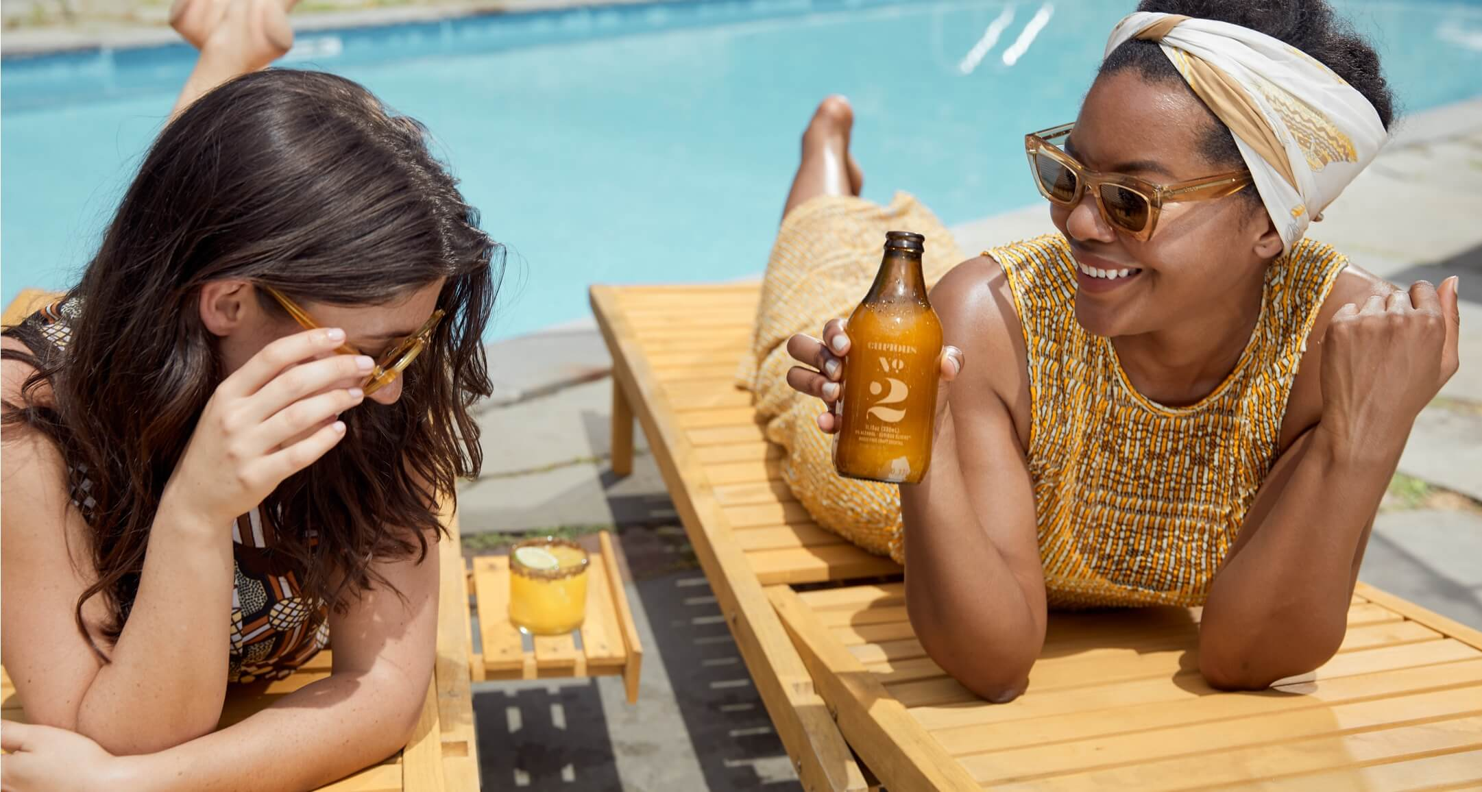 A photo of two women hanging out next to a pool, enjoying a refreshing Curious Elixirs alcohol-free cocktail