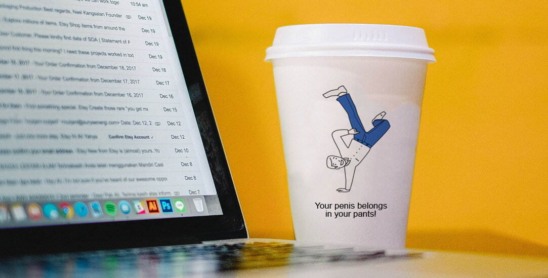 A photograph of a paper coffee cup next to a computer, the coffee cup has a cartoon man doing a handstand and the slogan 'Your penis belongs in your pants!'